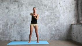 Йога молодой красивой женщины практикуя крытая