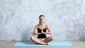 Йога молодой привлекательной женщины практикуя, делая Padmasana, представление лотоса внутри во всю длину акции видеоматериалы