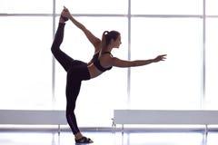 Йога молодой привлекательной женщины практикуя, стоя в Natarajasana стоковые фото
