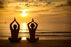 Йога молодых пар практикуя на пляже на заходе солнца стоковая фотография