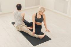 Йога молодых пар практикуя совместно в студии Стоковое фото RF