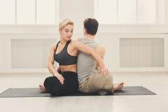 Йога молодых пар практикуя совместно в студии Стоковые Изображения