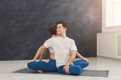 Йога молодых пар практикуя совместно в студии Стоковое Фото