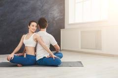Йога молодых пар практикуя совместно в студии Стоковые Фото
