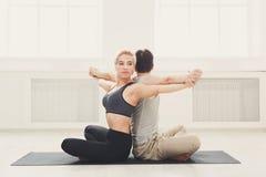 Йога молодых пар практикуя совместно в студии Стоковые Изображения RF