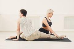 Йога молодых пар практикуя совместно в студии Стоковое Изображение RF