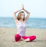 Йога молодой дамы практикуя Разминка около моря океана Стоковые Изображения RF