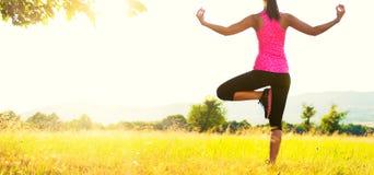 Йога молодой атлетической женщины практикуя на луге на заходе солнца Стоковые Изображения