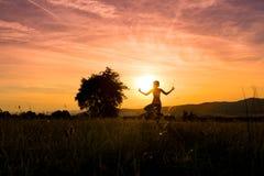 Йога молодой атлетической женщины практикуя на луге на заходе солнца Стоковые Фото