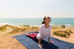Йога молодой женщины на пляже моря на здоровая жизнь Стоковые Фотографии RF