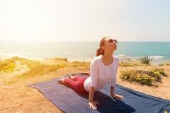 Йога молодой женщины на пляже моря на здоровая жизнь Стоковая Фотография