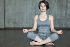 Йога молодой женщины практикуя на предпосылке серой бетонной стены Стоковые Изображения