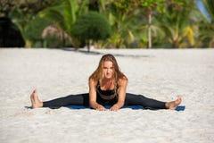 Йога молодой женщины практикуя на пляже Стоковое Изображение