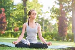 Йога молодой женщины практикуя outdoors на парке Стоковая Фотография RF