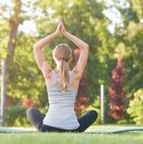 Йога молодой женщины практикуя outdoors на парке Стоковое Изображение RF