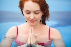 Йога молодой женщины redhead практикуя с руками в Namaste и держит ваши глаза закрытый Кавказская женщина размышляя в стоковое фото rf