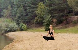 Йога молодой красивой женщины практикуя на озере леса, здоровом li Стоковая Фотография