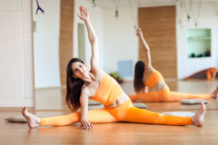 Йога молодой привлекательной счастливой женщины yogi практикуя, оранжевый костюм, во всю длину Стоковые Изображения RF