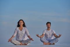 Йога молодых пар практикуя Стоковая Фотография