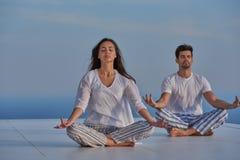 Йога молодых пар практикуя Стоковая Фотография RF