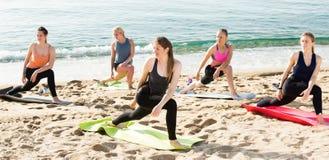 Йога на пляже моря, группе в составе тренировка женщин Стоковая Фотография RF