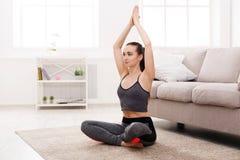 Йога дома, женщина делает представление лотоса Стоковые Изображения