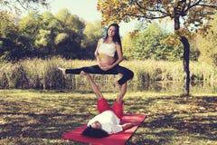 Йога осени в человеке и беременной женщине парка делая йогу acro Стоковое Фото