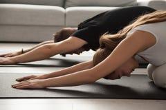 Йога пар практикуя в представлении ребенка ослабляя на циновке совместно Стоковые Изображения RF