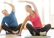 Йога подходящих пар практикуя на циновке дома стоковые изображения rf