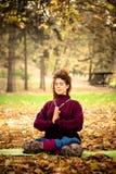 Йога практики женщины в парке осени Стоковые Изображения