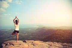 Йога практики женщины на скале горного пика Стоковое фото RF