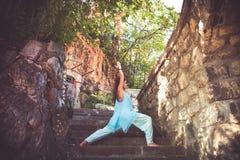 Йога практики женщины на старых лестницах внешних стоковые фото