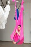 Йога представления лотоса девушки воздушная антигравитационная Женщина сидит в гамаке Стоковая Фотография RF