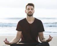 Йога человека практикуя на пляже Стоковая Фотография