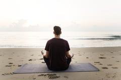 Йога человека практикуя на пляже Стоковые Фото