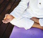 Йога человека практикуя outdoors на циновке йоги Стоковая Фотография