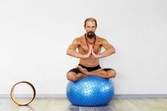 Йога человека Yogi практикуя на шарике фитнеса в представлении лотоса Стоковое фото RF