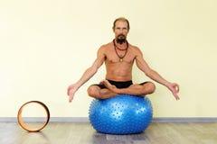 Йога человека Yogi практикуя на шарике фитнеса в представлении лотоса Стоковые Фото