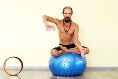 Йога человека Yogi практикуя на шарике фитнеса в представлении лотоса Стоковые Изображения