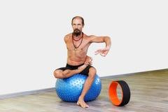 Йога человека Yogi практикуя с шариком фитнеса Стоковые Фото