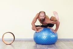Йога человека Yogi практикуя с шариком фитнеса Стоковое Фото