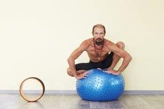 Йога человека Yogi практикуя с шариком фитнеса Стоковые Фотографии RF