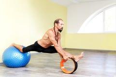 Йога человека Yogi практикуя с pilates звенит и шариком фитнеса Стоковое фото RF