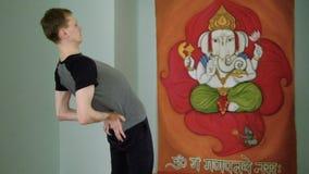 Йога человека делает здоровый протягивать в студии сток-видео
