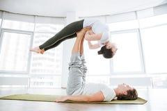 Йога acro мирной женщины практикуя с партнером Стоковые Фотографии RF