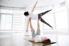 Йога acro милой молодой женщины практикуя с партнером Стоковое Изображение RF