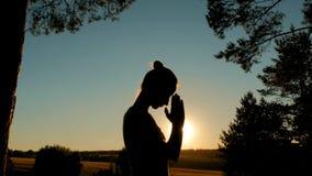 Йога Sporty женщины практикуя в парке на заходе солнца стоковое изображение