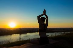Йога Sporty женщины практикуя на заходе солнца - грейте на солнце salutation Стоковые Изображения