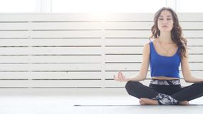 Йога Sporty молодой женщины практикуя, сидя в половинной тренировке лотоса, представление Siddhasana, крытая, домашняя внутренняя сток-видео