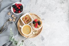 Йогурт здоровой чашки кофе завтрака греческий с домодельным Granola, ягоды, поленики и ежевики работают ноутбук стоковая фотография
